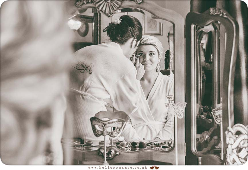 Bride having make-up done in mirror - www.helloromance.co.uk