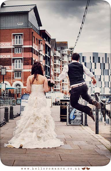 Bride and Groom walking jumping having fun in Ipswich on wedding day at Isaac Lord Ipswich Waterfront Isaac's Suffolk Unique Vintage wedding photography - Hello Romance Wedding Photography