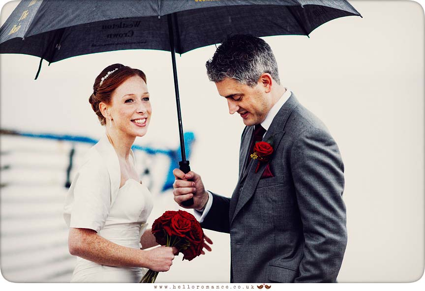 Bride and Groom in rain on Dunwich Beach with umbrellas - Westleton Crown Wedding Photography - Kate and Rob - Hello Romance Wedding Photography Suffolk
