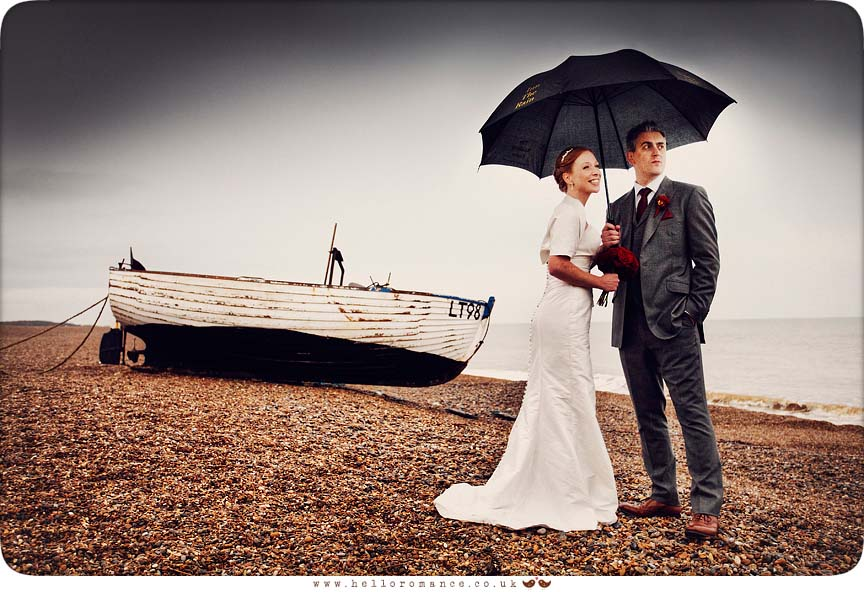 Bride and Groom in rain on Dunwich Beach with umbrellas with boat dark sky- Westleton Crown Wedding Photography - Kate and Rob - Hello Romance Wedding Photography Suffolk