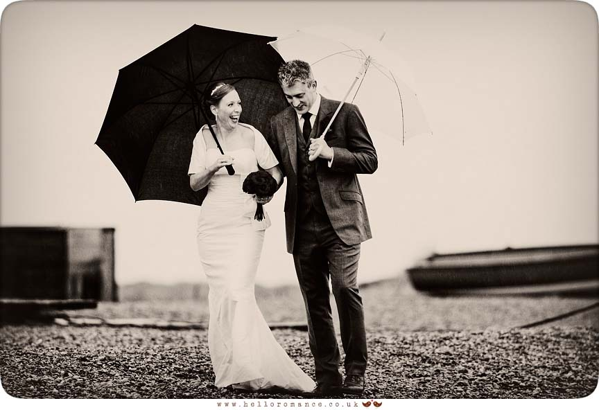 Bride and Groom walking in rain on Dunwich Beach with umbrellas - Westleton Crown Wedding Photography - Kate and Rob - Hello Romance Wedding Photography Suffolk