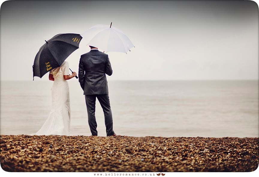 Bride and Groom standing in rain on Dunwich Beach with umbrellas - Westleton Crown Wedding Photography - Kate and Rob - Hello Romance Wedding Photography Suffolk