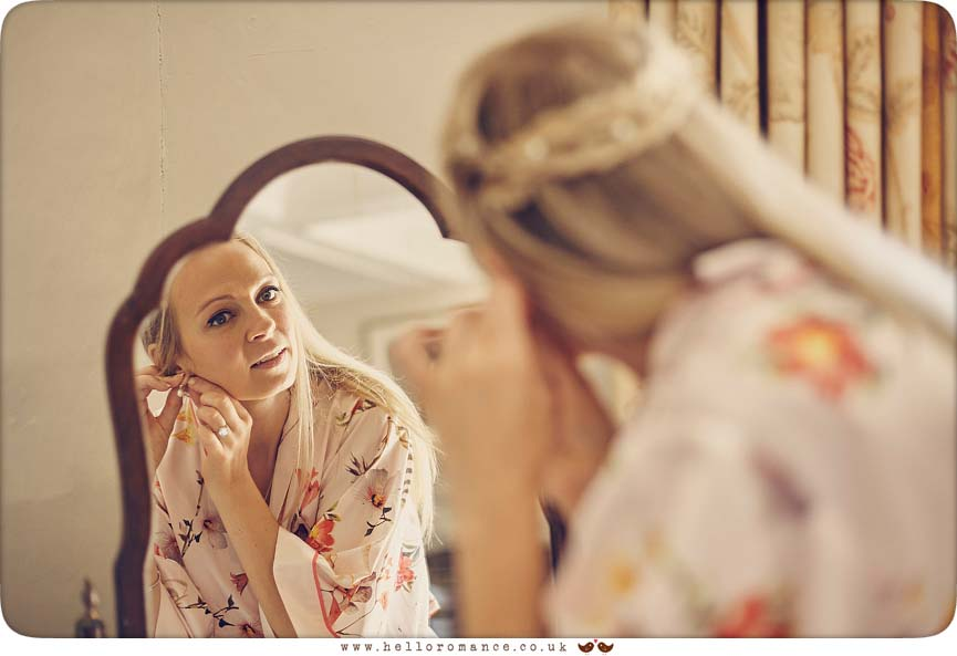 Bride putting on earrings in mirror at Bruisyard Hall - www.helloromance.co.uk