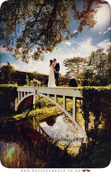 Bride and Groom on bridge outside gardens with sun flare at Helmingham Hall Wedding Photography - Katie and Greg - Hello Romance Wedding Photography Ipswich Suffolk