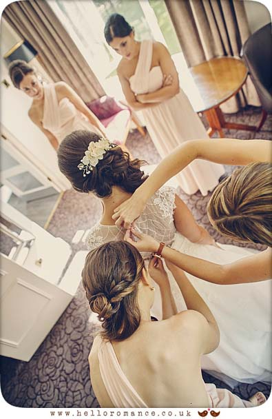 Bride being helped into dress by bridesmaids Pontland's park Essex - www.helloromance.co.uk
