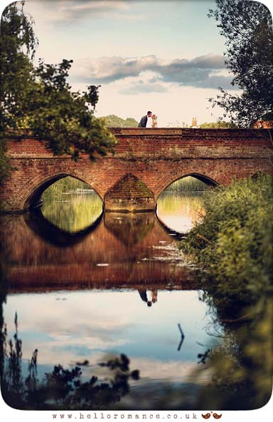Bride and Groom leaning in for kiss on Toppesfield bridge, Hadleigh Suffolk Unique Vintage wedding photography - Hello Romance Wedding Photography