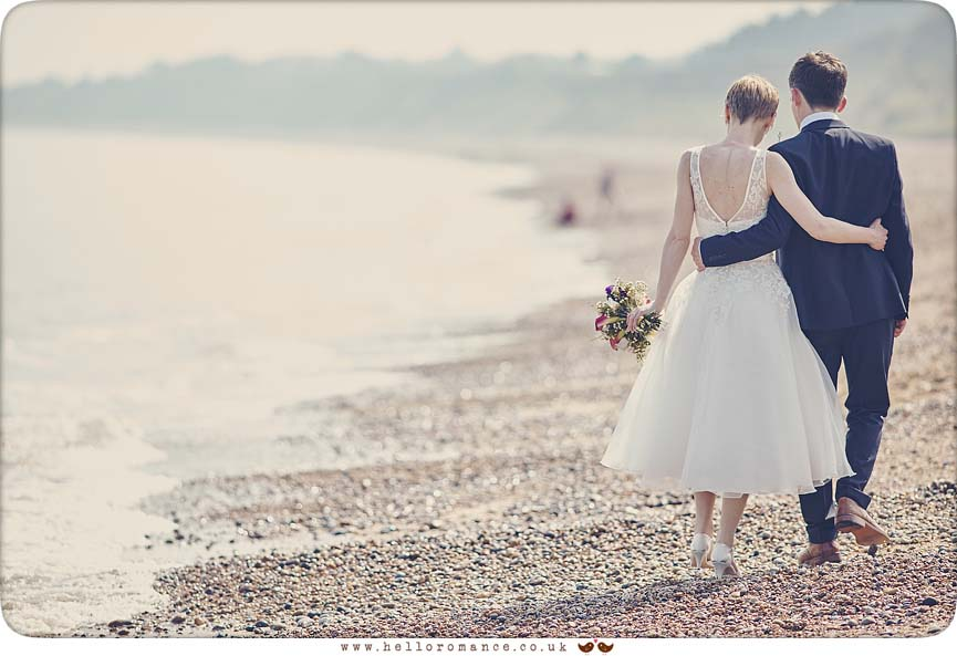 Bride and groom romantically walking along sea shore in Suffolk - www.helloromance.co.uk