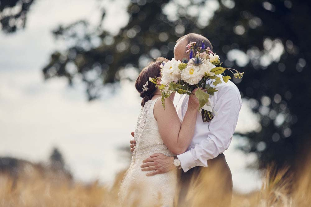 kissing behind bouquet, fun wedding photo of bride and groom - www.helloromance.co.uk