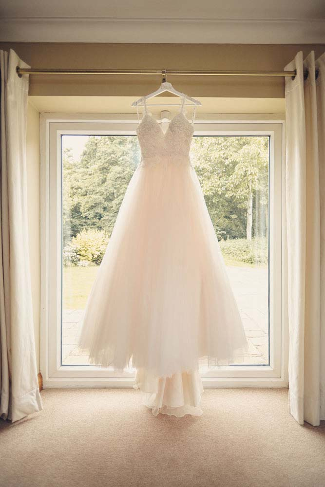 Wedding Dress hung up by window - www.helloromance.co.uk