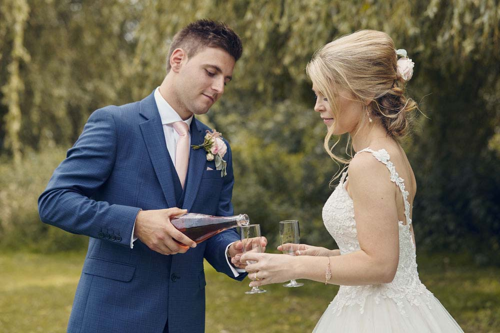 Groom pouring champagne for bride - www.helloromance.co.uk