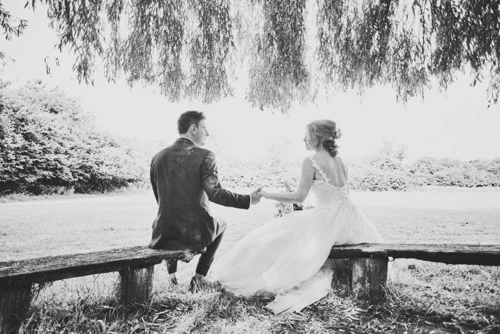 Romantic photo of bride and groom under willows, on benches, Sproughton Tithe Barn, Suffolk Wedding photography - www.helloromance.co.uk