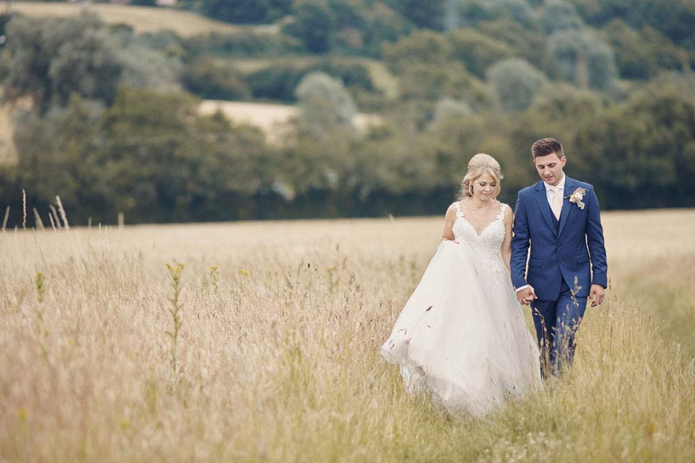 Bride and groom walking through long grass in field - www.helloromance.co.uk