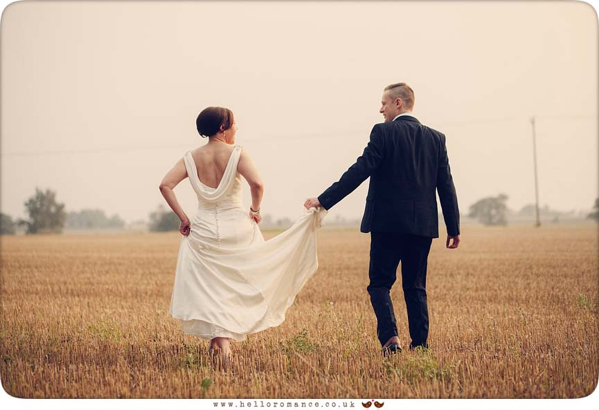 Bride and groom stepping through harvested wheat field at sunset - www.helloromance.co.uk