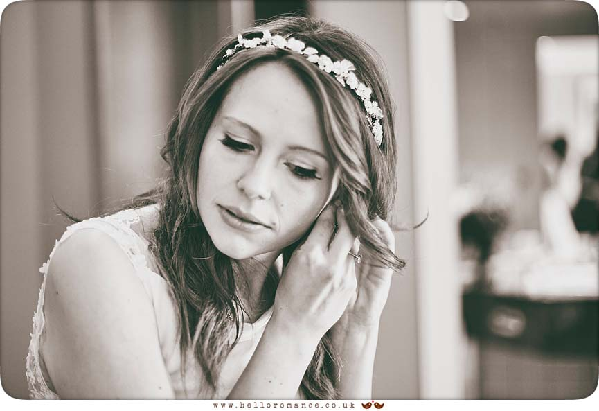 Beautiful black & white photo of bride putting earrings on - www.helloromance.co.uk