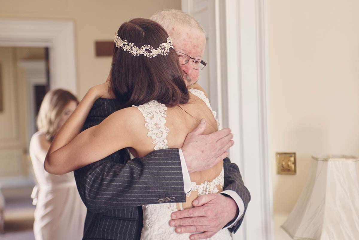 Father of the bride embraces bride at Hintlesham Hall - www.helloromance.co.uk