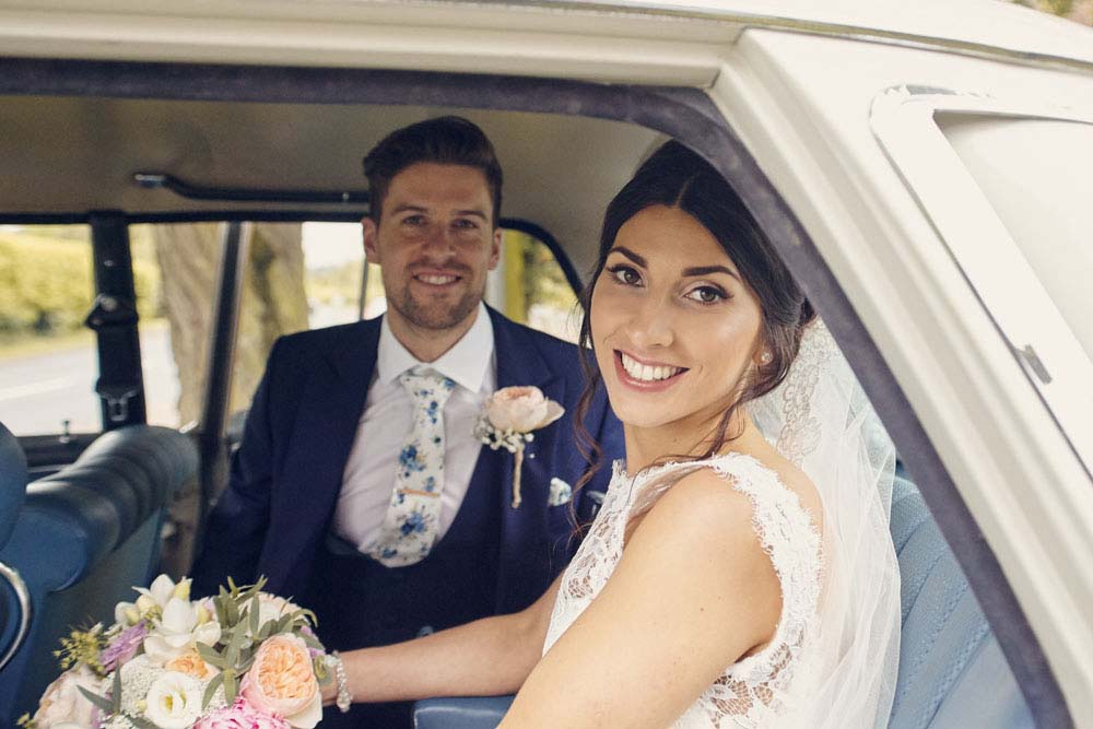 bride and groom in back of wedding car - www.helloromance.co.uk