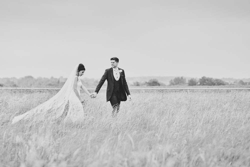 black and white bride and groom in meadow landscape at Moreves Barn in Sudbury Suffolk - www.helloromance.co.uk