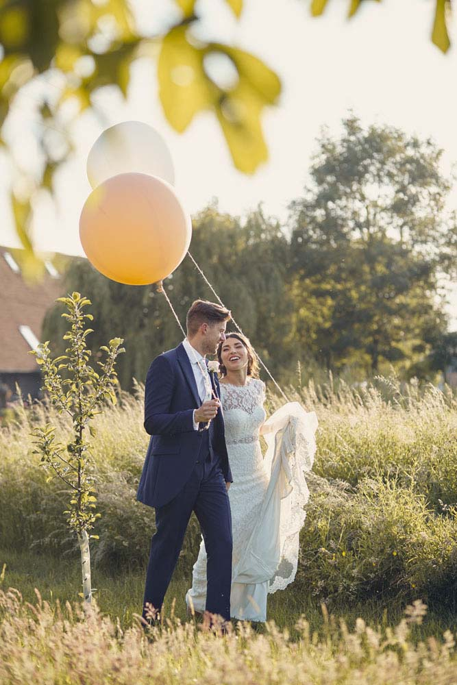 bride and groom taking balloons for a walk at Moreves Barn in Sudbury Suffolk - www.helloromance.co.uk