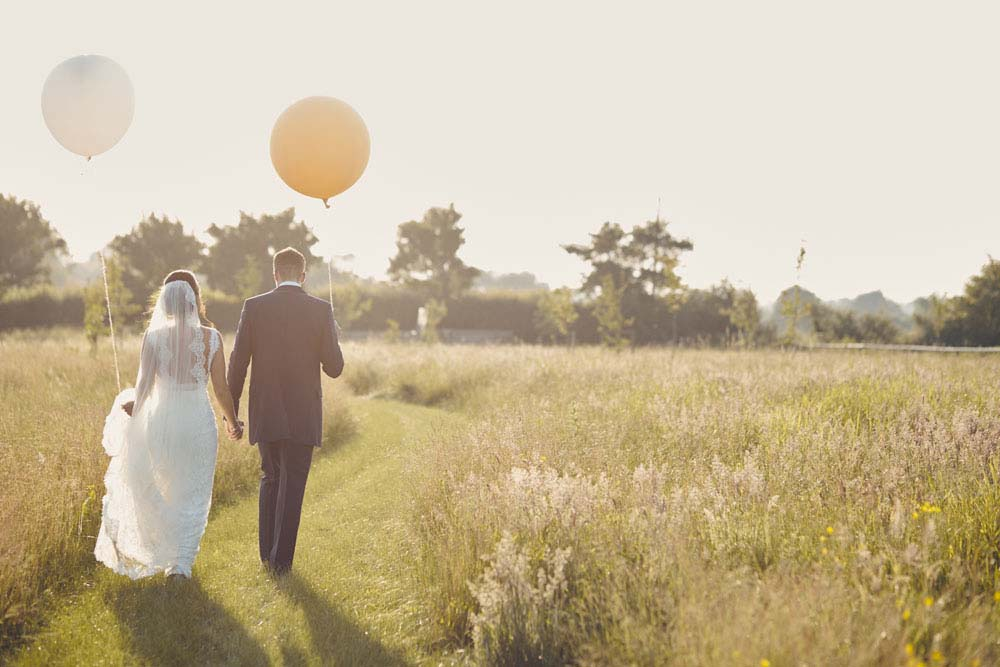 bride and groom walking into sunset at Moreves Barn in Sudbury Suffolk - www.helloromance.co.uk