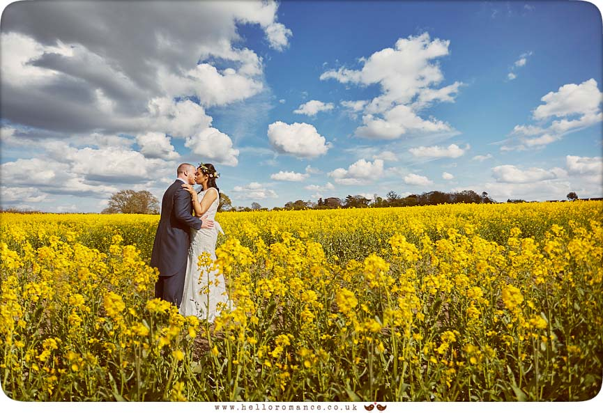 Bride and groom in field of yellow rapeseed oil field - www.helloromance.co.uk