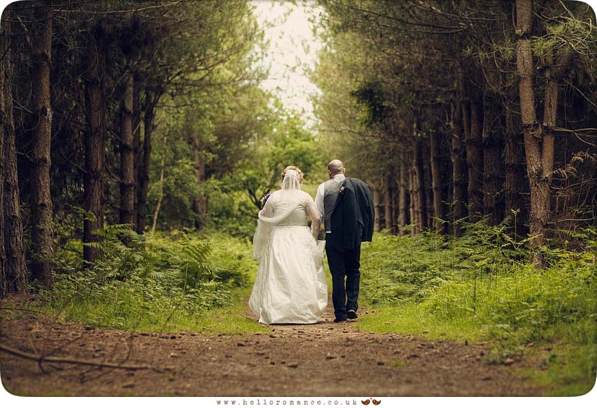 Cute English Wedding Photos Suffolk Vintage Toned Walking away aisle of trees - Hello Romance