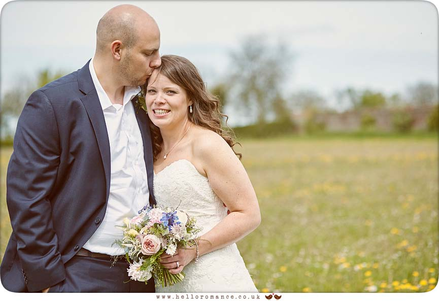 Groom kisses bride's head in Suffolk meadow - www.helloromance.co.uk