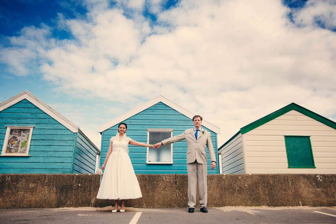 Bride and Groom with Beach Huts - helloromancephotography.com